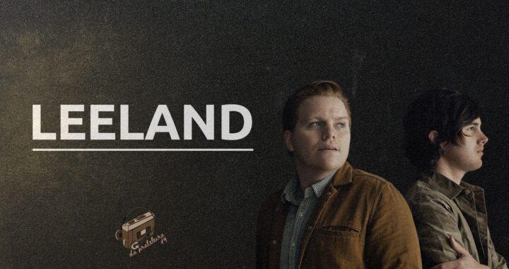 """Fundo preto. Na frente o título do episódio, como o nome da banda """"Leeland"""" em branco. Do aldo direito a foto de dois rapazes, membros da banda."""